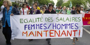 "A woman holds a banner reading ""Equal pay women/men now"" as people take part in a march as part of the annual May Day workers' events on May 1, 2011 in Paris. Hundreds of thousands of people around the world attended May Day rallies today to defend workers' rights many say are under fresh attack, and to press for social justice and democratic reform. From Hong Kong to Indonesia, Moscow to Paris, protesters marched and rallied in largely peaceful demonstrations for international Labour Day. AFP PHOTO / MIGUEL MEDINA (Photo credit should read MIGUEL MEDINA/AFP/Getty Images)"